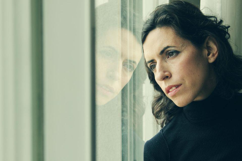 Psychologie: Eine nachdenkliche Frau am Fenster