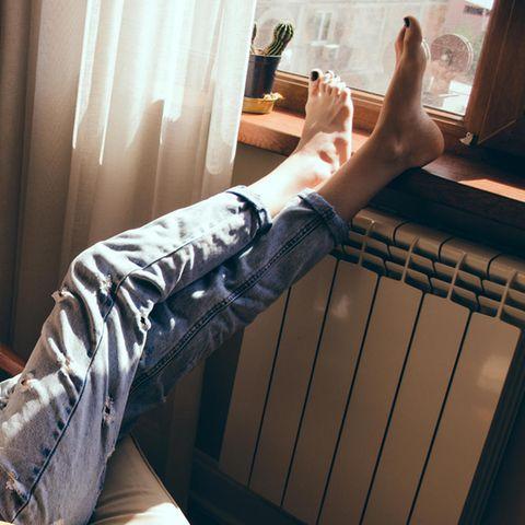 Eine Frau sitzt in einem Sessel, trinkt aus einer Tasse und legt die Füße auf einen Heizkörper