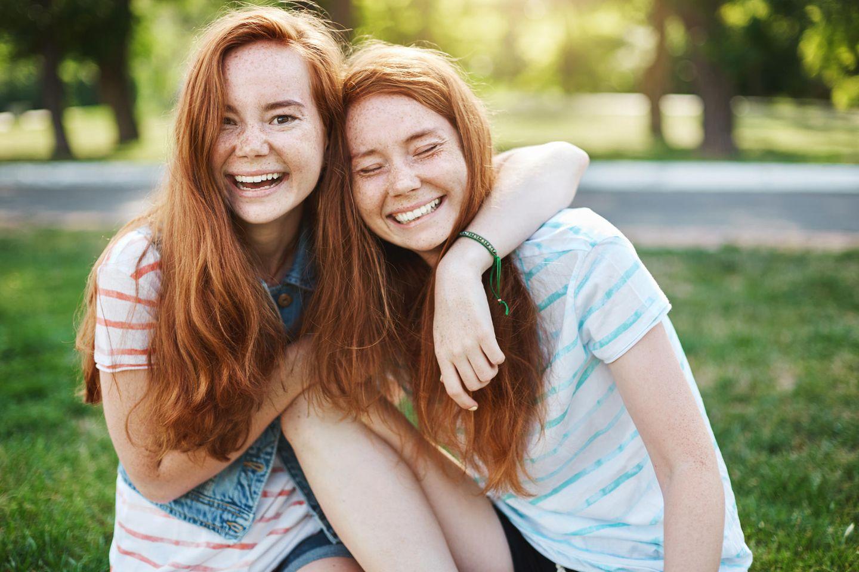 Zwillinge: Schwestern umarmen sich lachend