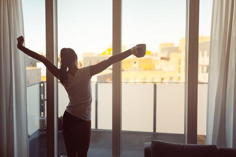 Eine Frau steht vor dem Fenster und reckt die Arme in die Luft mit einer Tasse Kaffee in der Hand