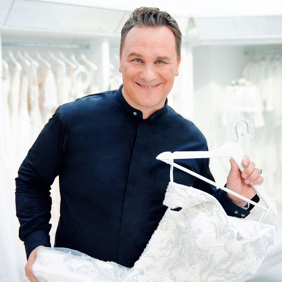 Guidos Wedding Race: Guido hält ein Brautkleid.