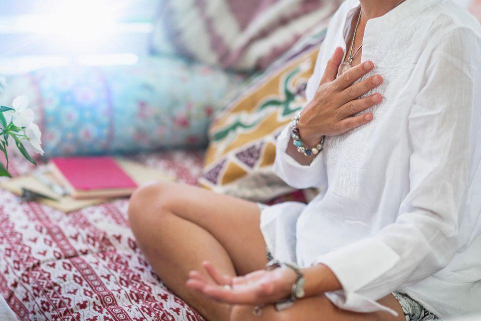 Metta-Meditation: Frau meditiert mit Hand auf dem Herzen
