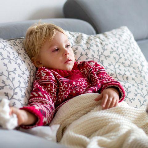 RS-Virus beim Kleinkind: Kranker kleiner Junge liegt gut zugedeckt auf dem Sofa