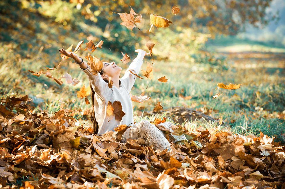 Glückspilze: Lachendes Mädchen wirft Blätter in die Luft