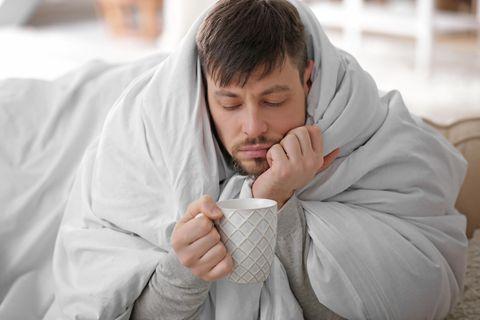 Männergrippe: Mann mit Decke und Tee