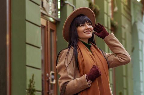 Eine Frau mit Pony-Frisur hält ihren Hut und schaut verträumt in die Luft.