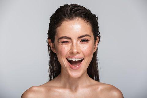 Frau mit nassen Haaren und Gesicht Augenzwinkern
