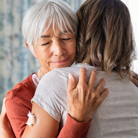 Mutter umarmt Tochter mit Impfpflaster