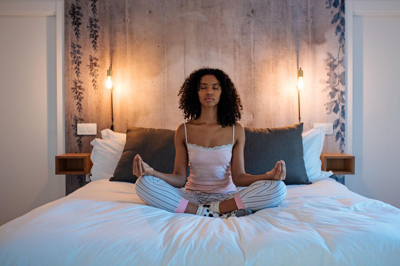 Meditation zum Einschlafen: Frau meditiert im Pyjama auf dem Bett