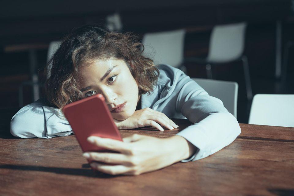 FOMO: Mädchen stützt sich energielos auf den Tisch mit Smartphone in der Hand