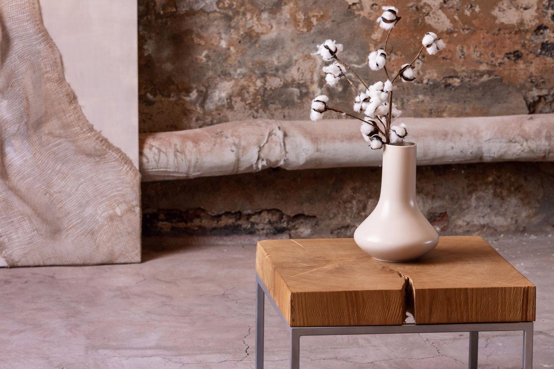 Wabi-Sabi: Eine Vase mit Baumwoll-Zweigen steht auf einem Beistelltisch