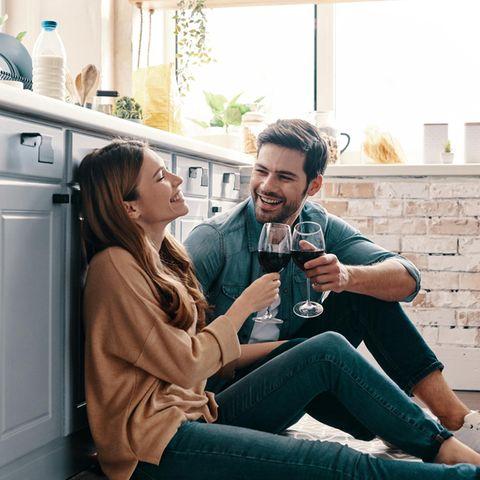 Eine Frau und ein Mann sitzen glücklich in der Küche und stoßen mit Wein an