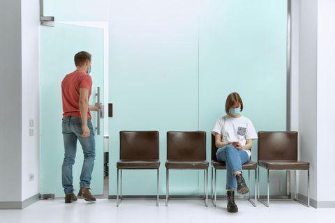 Eine Frau wartet im Wartezimmer eines Arztes, während ein Mann bereits aufgerufen wurde