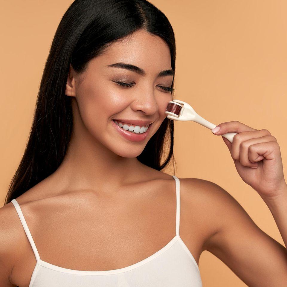 GLOSSIP: Expertin verrät: Was es mit Beautification auf sich hat: Brünette benutzt ein Gesichts-Tool
