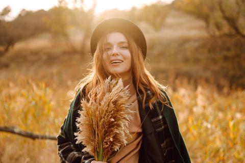 Horoskop: Eine fröhliche Frau auf dem Feld