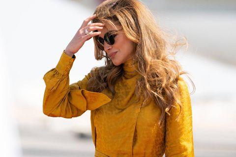 Königin Rania hält sich ihre Haare aus dem Gesicht.