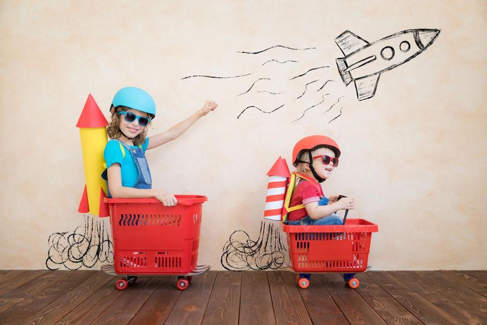 Zwei Kinder sitzen in Einkaufskörben und spielen Astronauten