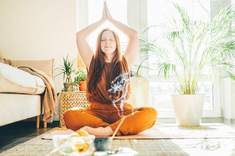 Das sind die 5 größten Mythen über Yoga: Frau übt zu Hause Yoga mit Räucherstäbchen.