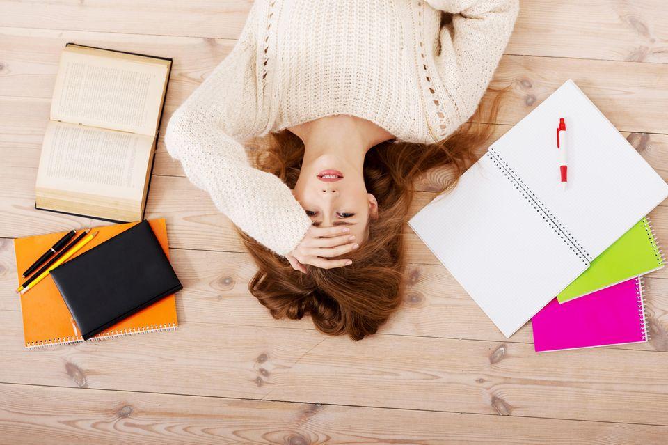 Stress-Gefühle: Junge Frau liegt auf dem Boden umgeben von Lernmaterial