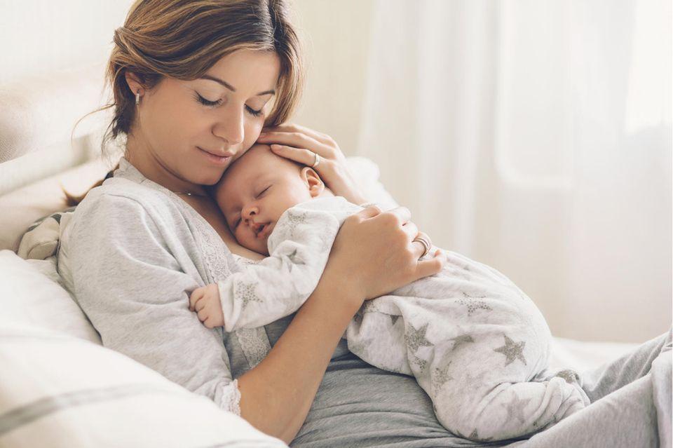 Liegende Mama mit schlafendem Baby auf der Brust