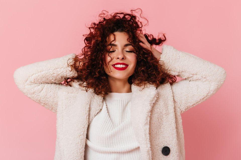 TikTok Hack für voluminöse Haare: Eine Frau fährt sich durch ihre Haare und lächelt dabei.
