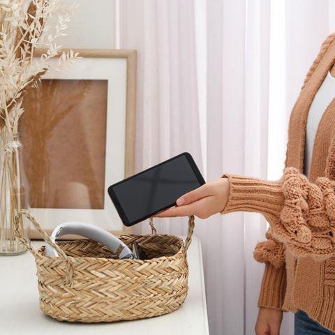 Eine Frau legt ihr Handy in einen Korb.
