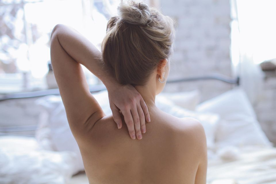Eine Frau berührt ihren Rücken.