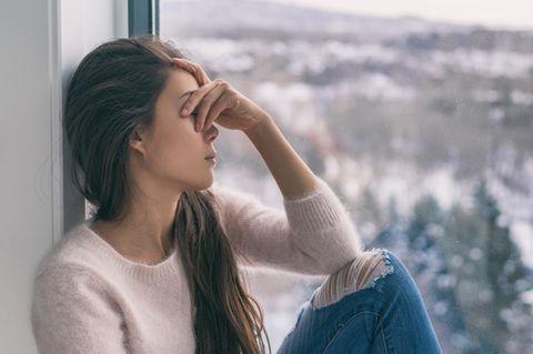 Frau sitzt einsam am Fenster