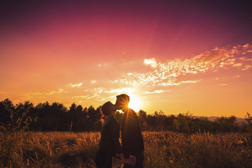Beziehung: Ein Paar küsst sich im Sonnenuntergang