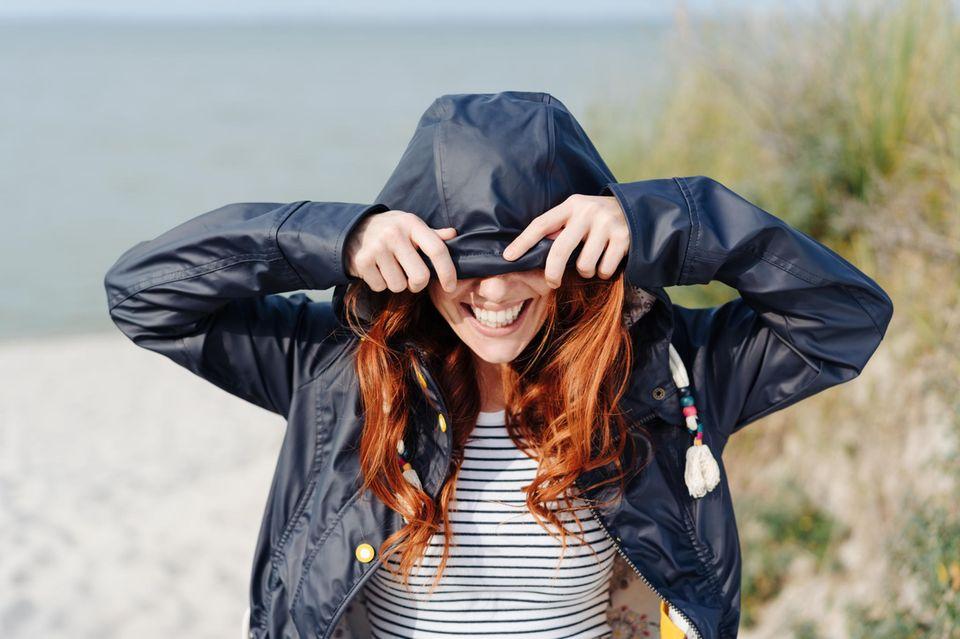 Horoskop: Lachende Frau mit Regenschirm im Regen