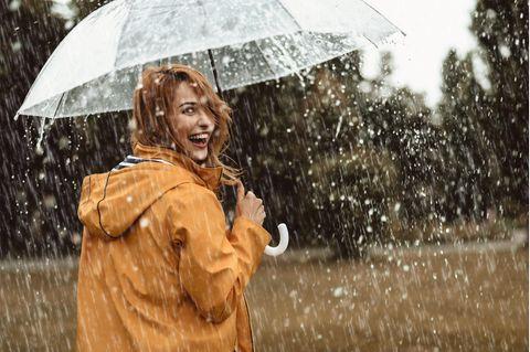Horoskop ab 22.10.2021: Frau mit Schirm gut gelaunt im Regen