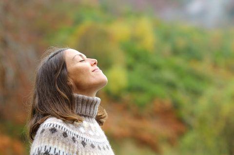 Horoskop: Frau mit geschlossenen Augen genießt das Wetter