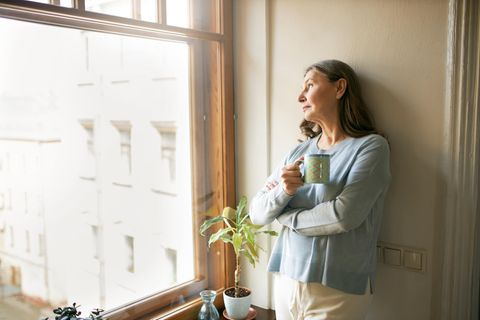 Diese 6 Lebensmittel können die Wechseljahre verschlimmern: Frau schaut mit Becher in der Hand aus dem Fenster.