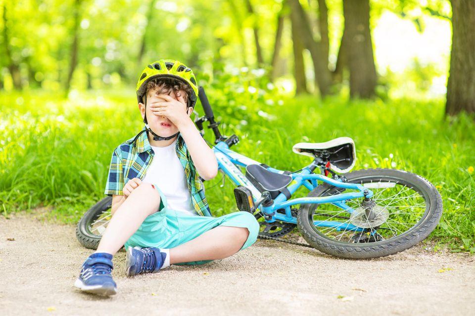 Radfahren lernen: Junge weint neben seinem Fahrrad