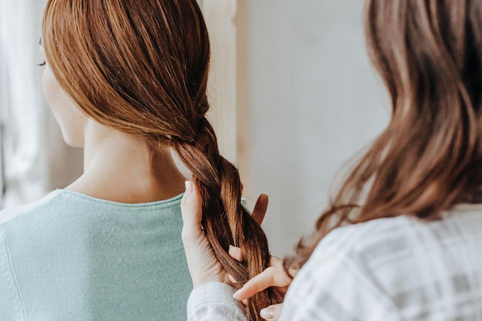 Schöne Herbst-Frisur: Eine Frau flechtet einer anderen Frau die Haare.