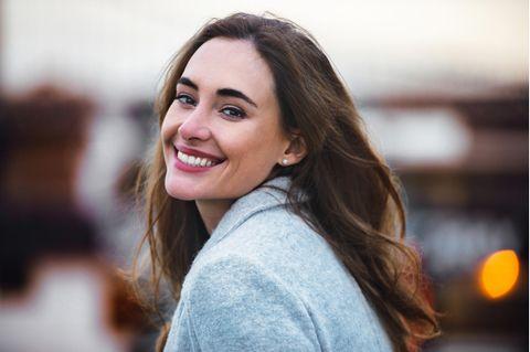 Lachende Frau mit langem braunem Haar