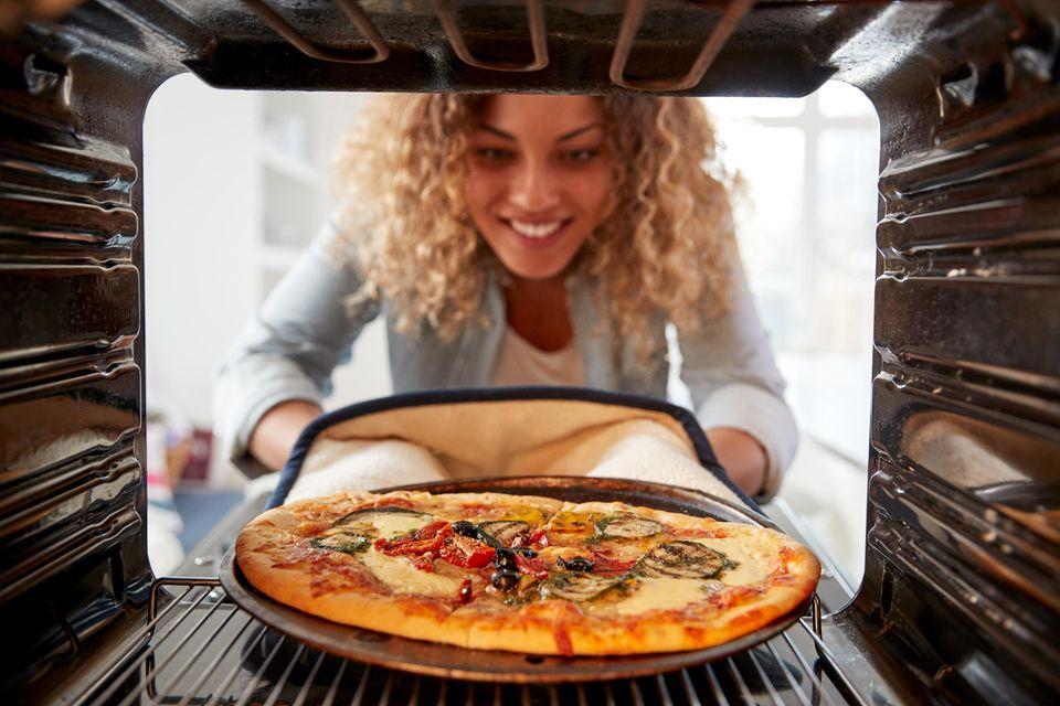 Eine Frau nimmt eine Pizza aus dem Ofen.