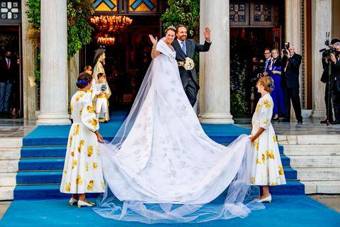 Nina Flohr und Prinz Philippos von Griechenland haben Ja gesagt. Bei der Trauung in Athen begeistert die Braut (hier an der Seite ihres Vaters) mit einem glamourösen Kleid mit floralen Stickereien und einer großen Schleife am Dekolleté. Ein weiteres Highlight: die XXL-Schleppe und der noch längere Schleier.
