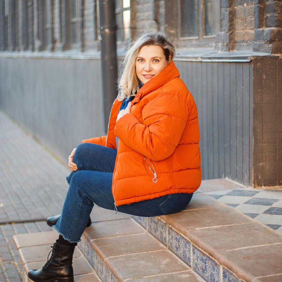 Frau mit orangener Daunenjacke