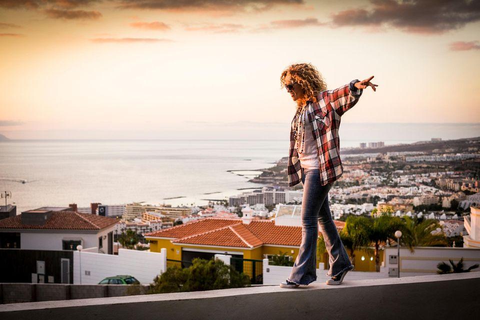 Psychologie: Eine Frau balanciert über eine Mauer