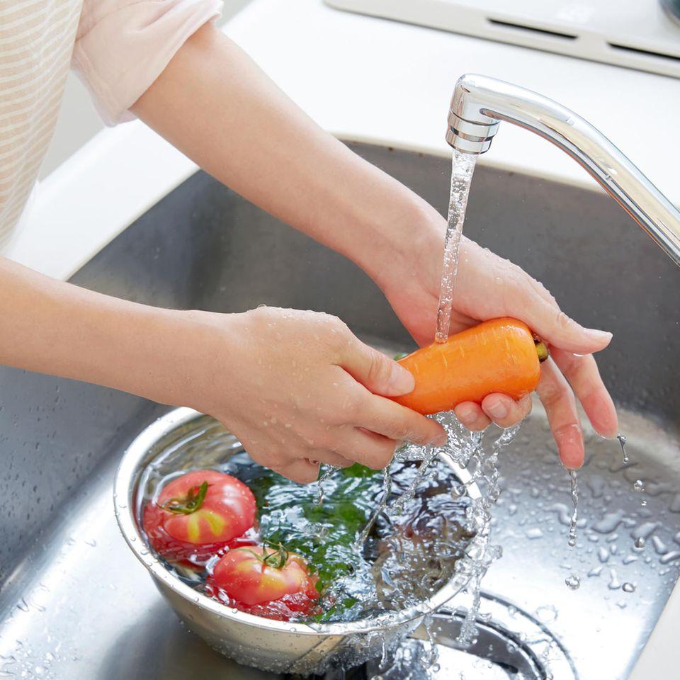 Gemüse wird unter Wasserstrahl gewaschen