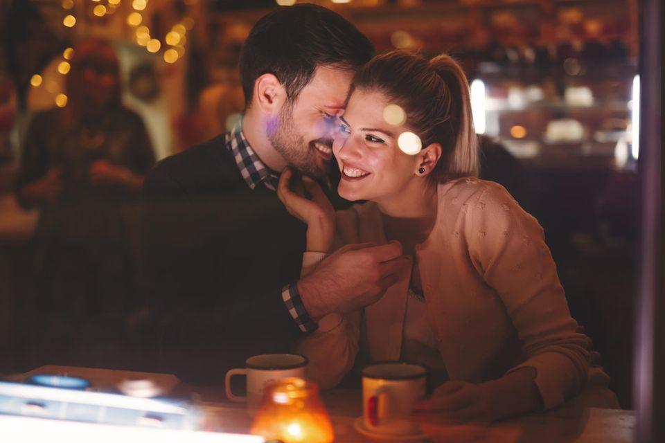 Ein verliebtes Paar kuschelt auf einem Date im Restaurant.