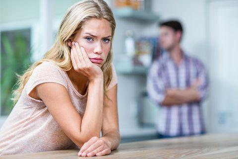 Eine Frau stützt nachdenklich den Kopf in ihre Hand während ein Mann im Hintergrund auch nachzudenken scheint.