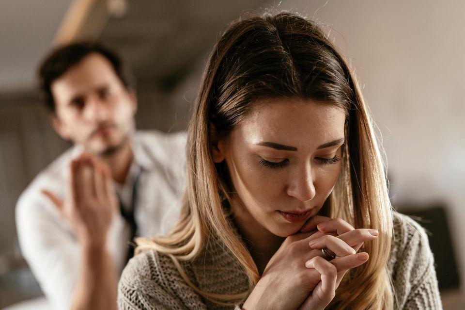 Eine verzweifelte Frau wird von einem Mann angeschrien