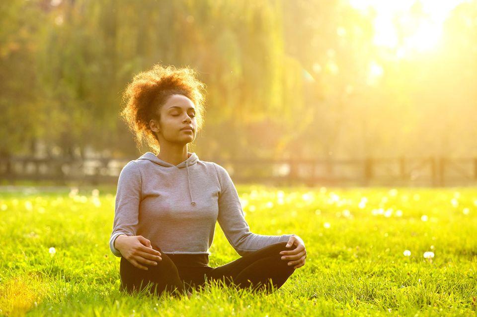 3 Missverständnisse über Meditation – und wie es wirklich ist: Frau meditiert draußen auf einer Wiese.