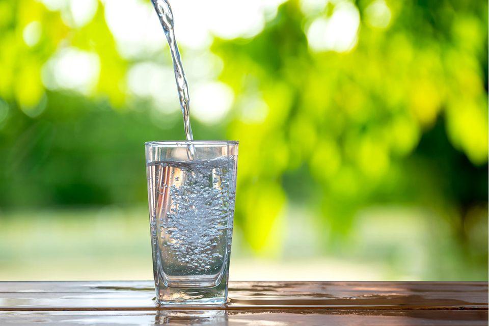 Wasserflecken entfernen: Glas Wasser und Wasserflecken auf einem Holztisch