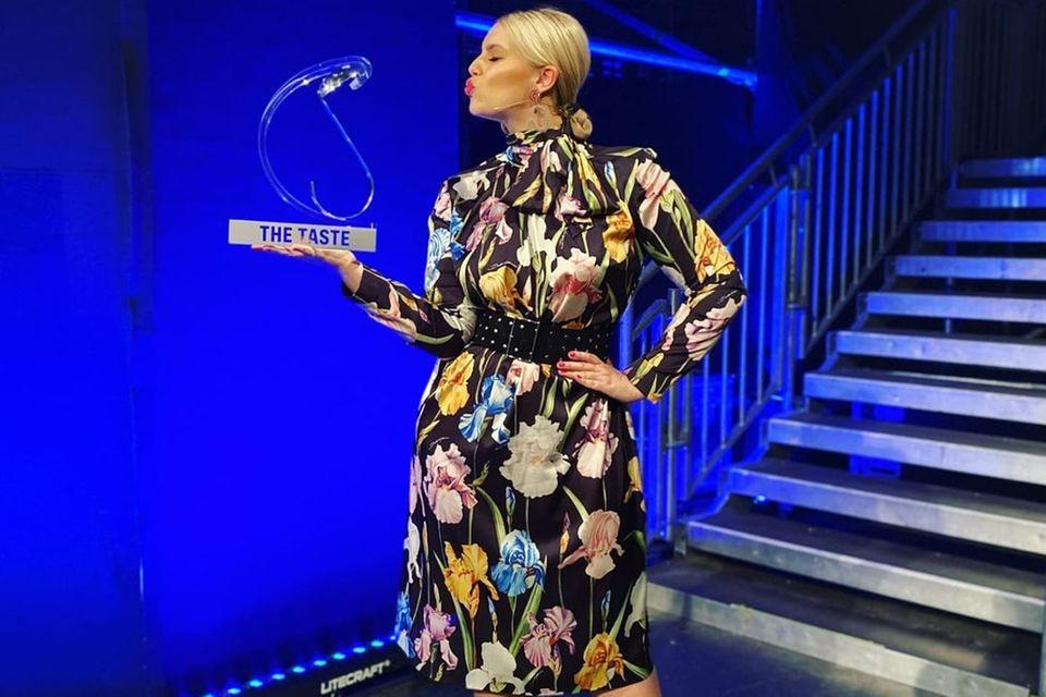 """Für das Finale von """"The Taste"""" hat sich Moderatorin Angelina Kirsch besonders schick gemacht. Für die TV-Aufzeichnung hat sich das Model ihr Kleid sogar extra anfertigen lassen. Das fließende Kleid mit Blumenprint kombiniert sie mit einem Gürtel, der ihre Kurven perfekt in Szene setzt. Nur bei der Schuhwahl hätte sich Angelina Kirsch lieber für ein anderes Modell entschieden. Denn das Grün ihrer Sandaletten beißt sich unangenehm mit dem Grüntön auf ihrem Kleid. Das kann die sympathische Blondine definitiv besser!"""